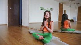 A menina está sentando-se na posição de lótus no gym video estoque