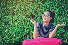 A menina está sentando-se na rua com sua mala de viagem cor-de-rosa t pronto foto de stock royalty free