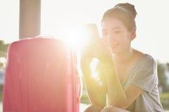 A menina está sentando-se na rua com sua mala de viagem cor-de-rosa t pronto imagens de stock royalty free