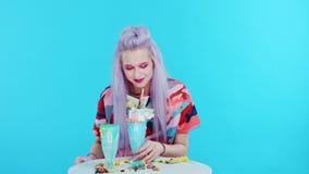 A menina está sentando-se na tabela com um olhar furado Traga o freakshake que é surpreendida retirar o smartphone e filme
