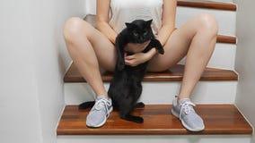 A menina está sentando-se nas escadas na casa entre seus pés está guardando um gato preto e está afagando-o filme