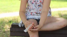 A menina está sentando-se no banco e está limpando-se seus pés com o tecido molhado filme