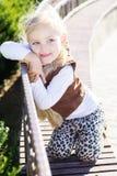 A menina está sentando-se no banco, tempo do outono Foto de Stock Royalty Free