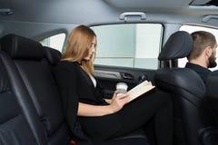 A menina está sentando-se no carro com um caderno imagem de stock royalty free