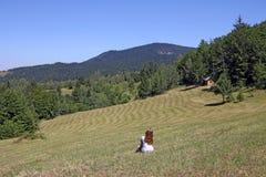 A menina está sentando-se no prado Fotografia de Stock
