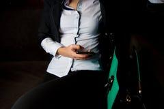 A menina está sentando-se no sofá perto do saco e está guardando-se o telefone fotografia de stock royalty free