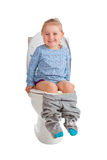 A menina está sentando-se no toalete imagens de stock royalty free