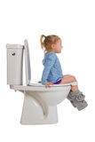 A menina está sentando-se no toalete fotografia de stock royalty free