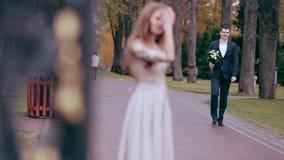 A menina está sozinha De trás vem um indivíduo com flores vídeos de arquivo