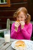 A menina está tendo o almoço foto de stock