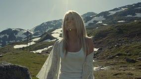 A menina está tendo o divertimento e está sorrindo na câmera, montanhas com neve no fundo, natureza bonita vídeos de arquivo