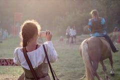A menina está tomando uma foto no festival de Tustan em Urych, Ucrânia, Au fotografia de stock
