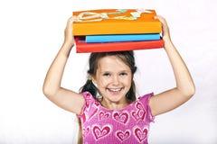 A menina está carreg livros Fotos de Stock