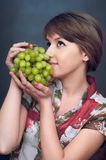 A menina está querendo uvas verdes Foto de Stock