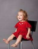A menina está sentando-se na cadeira no estúdio Imagens de Stock Royalty Free