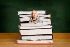 Menina estalando fora da pilha dos livros Foto de Stock