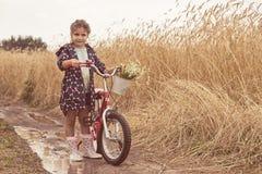 Menina a estar no campo com bicicleta Foto de Stock Royalty Free