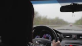 A menina estava conduzindo quando a chuva estava caindo Conduzir na estrada em chuvas pesadas deve ser cautelosa Chuvas pesadas s vídeos de arquivo