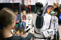 A menina estica para fora sua mão ao robô como um sinal do amigo Fotografia de Stock Royalty Free