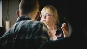 A menina europeia bonita nova nos vidros aprecia comer a pizza e falar em uma festa em casa ocasional com amigos video estoque