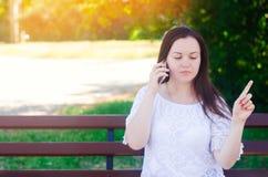 Menina europeia bonita nova que senta-se em um banco e que fala no telefone A menina aponta um dedo afastado, dá o conselho e o d foto de stock