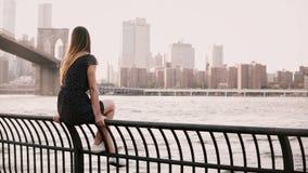 Menina europeia bonita que senta-se na cerca da terraplenagem do rio, olhando para trás na câmera que sorri perto da ponte de Bro vídeos de arquivo