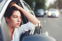 Menina europeia bonita que senta-se pensativamente na roda do carro fotografia de stock