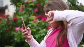 Menina europeia com o cabelo louro que toma imagens dsi mesma em seu smartphone