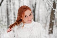 Menina europeia do gengibre na camiseta branca na neve dezembro da floresta do inverno no parque Tempo bonito do Natal Fotografia de Stock Royalty Free