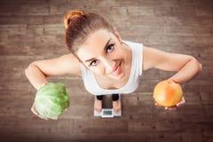 A menina europeia está em escalas e em guardar uma couve e um grapefr fotografia de stock