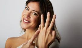 Menina europeia feliz com cabelo escuro longo na roupa à moda que sorri e que guarda a mão no quadril ao mostrar o casamento na m imagens de stock