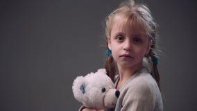 A menina europeia loura pequena com tranças que o penteado em uma camiseta bege realiza o urso de peluche branco, a seguir olha p video estoque