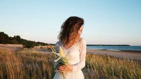 A menina europeia nova em um vestido de casamento está estando na grama com um ramalhete da noiva feito a mão da grama e do milho filme