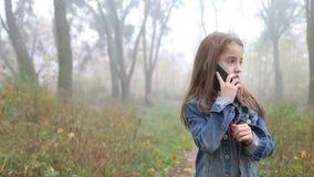 Menina europeia pequena com um cabelo longo, um casaco azul, umas calças pretas, umas sapatilhas e uns olhos azuis Uma criança pe video estoque