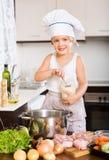 Menina europeia pequena que cozinha o alimento Fotos de Stock