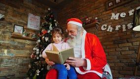 Menina europeia pequena que senta-se em joelhos em Santa Claus r fotos de stock royalty free