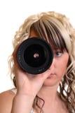 A menina examina o lense fotos de stock