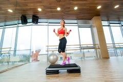 A menina executa a etapa cardio- com os pesos em um gym fotos de stock