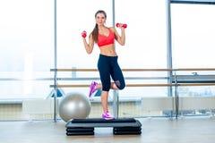 A menina executa a etapa cardio- com os pesos em um gym imagem de stock royalty free