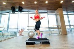 A menina executa a etapa cardio- com os pesos em um gym imagem de stock