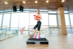 A menina executa a etapa cardio- com os pesos em um gym fotografia de stock