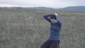 A menina expressivo em seus joelhos na grama é de grito e guardando sua cabeça, mo lento video estoque