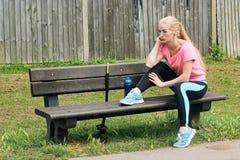 Menina exterior da aptidão que descansa em um banco Imagens de Stock Royalty Free