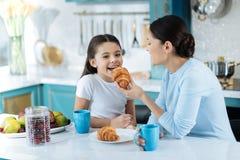 Menina exuberante que come cookies com sua mamã Foto de Stock Royalty Free