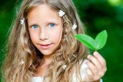 Menina eyed azul que guarda a folha verde. foto de stock royalty free