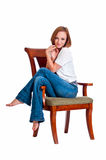 Menina eyed consideravelmente azul que relaxa em uma cadeira do braço. Imagens de Stock