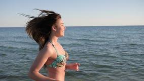 A menina fêmea, de cabelos compridos nova running 'sexy' corre ao longo do oceano filme