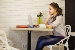 Menina fêmea de sorriso que senta-se na mesa e que olha no monitor do portátil Fotos de Stock Royalty Free