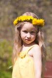 Menina fair-haired pequena na grinalda do dente-de-leão imagem de stock royalty free