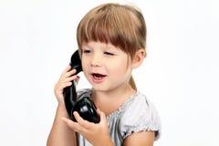A menina fala pelo telefone Fotografia de Stock Royalty Free